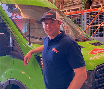 A man standing in front of a green vehicle.