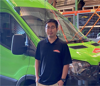 A man standing in front of a SERVPRO truck.