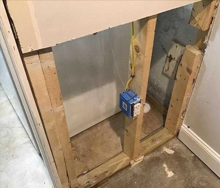 Inside a house where drywall has been removed to dry saturated wood studs
