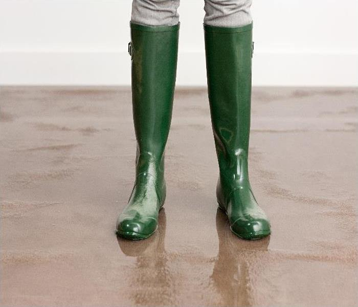 flood damaged home - image of boots on wet floor